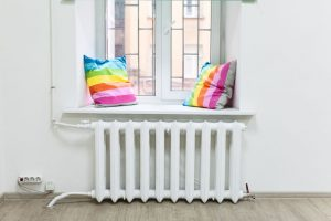 White iron radiator of central heating is under windowsill
