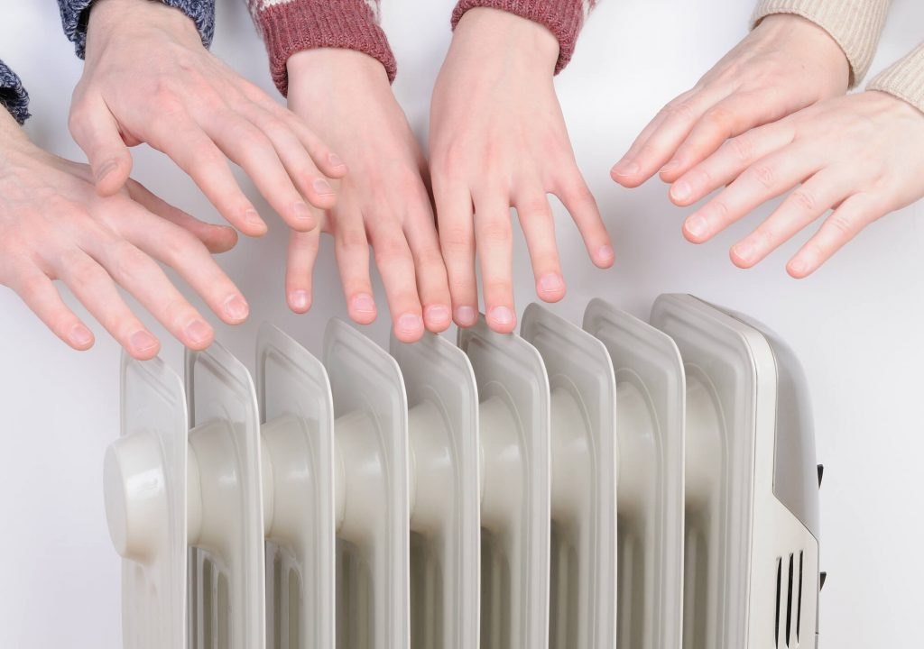 Family warm their hands on the radiator