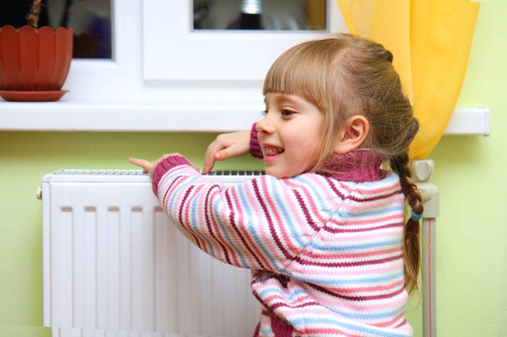 A little girl warm hands on radiator