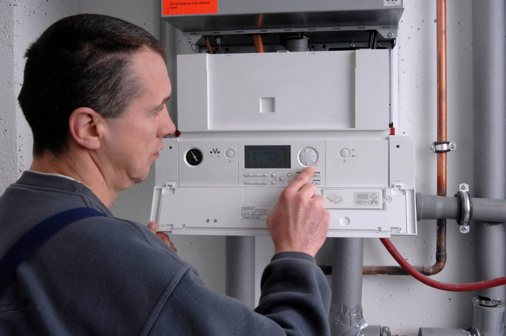 A heating engineer is checking the heating system